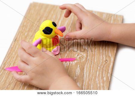 Children's hands mould a snowman from plasticine