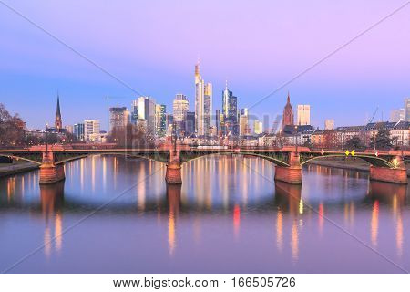 Picturesque view of Frankfurt am Main skyline and Ignatz Bubis Brucke bridge at sunrise with mirror reflections in the river, Germany