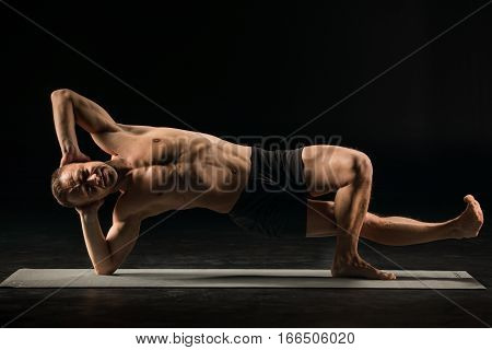 Athletic man practicing yoga in vasisthasana side plank variation
