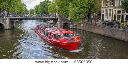 AMSTERDAM, NETHERLANDS - SEPTEMBER 18, 2016: Tourboat with tourists during a sightseeing tour of the canals of Amsterdam, Holland