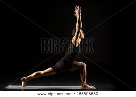 Man practicing yoga standing in variation of Warrior I posture or Virabhadrasana One pose