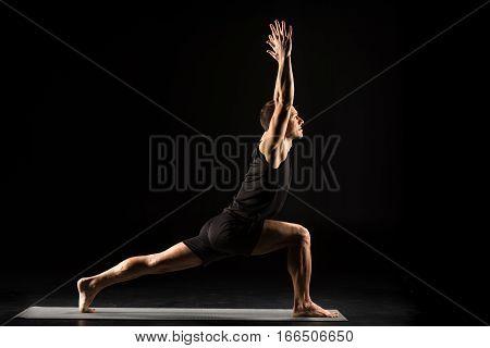 Man practicing yoga standing in variation of Warrior I posture or Virabhadrasana One pose