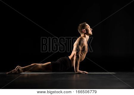 Man performing Bhujangasana ot Cobra Pose on yoga mat