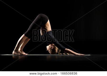 Woman performing Adho Mukha Svanasana or the downward facing dog pose