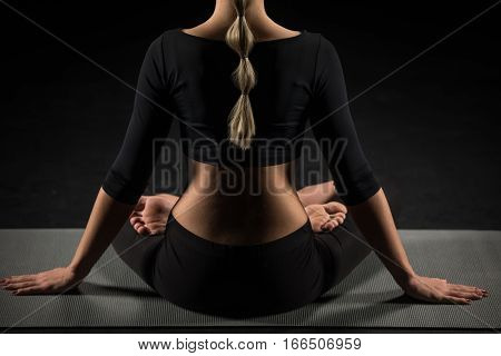 Partial rear view of woman performing Padmasana on yoga mat