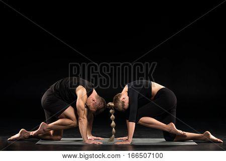 Couple performing Knee to Forehead exercise or Eka Pada Marjariasana on yoga mat