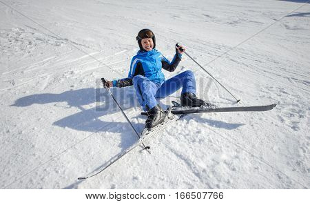 Young Female Skier After The Fall On Mountain Slope
