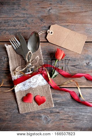 Valentines day label attached to cutlery inside a pouch with decorative ribbon and a single rose