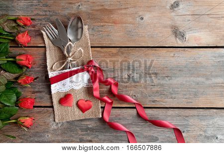 Valentines day cutlery set inside pouch with red roses and hearts over a wooden background