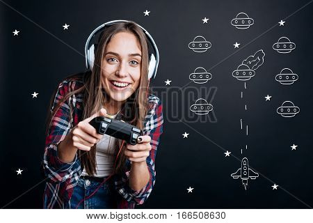 Open space. Delighted cheerful emotional woman smiling and holding game console while playing video games