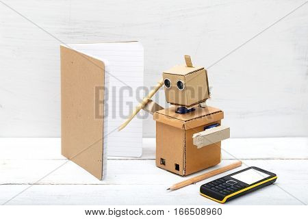 robot holding a pen and writing in a notebook. Artificial Intelligence