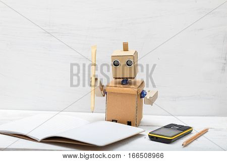 robot holding a pen and wrote in a notebook