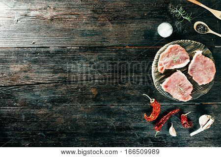 Meat steaks, raw, spices and potherbs on circle cutting board