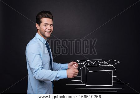 Box of gifts. Joyful delighted young man smiling and opening a box with presents while standing against isolated black background.