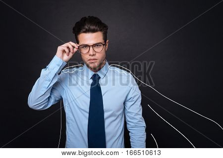Insightful look. Handsome serious young man wearing a cape and holding his glasses while standing against isolated black background.
