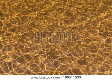 Golden sand ripples through wave of water Abstract background stock photo