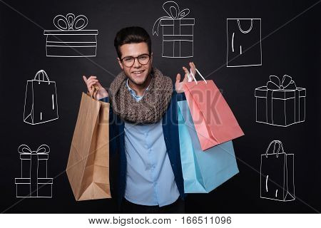 Delightful shopping. Handsome delighted young man smiling and holding shopping bags with presents while standing against isolated black background. poster
