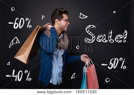 Delightful discounts. Happy handsome young smiling and holding items bought on sale while standing against isolated black background.