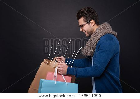 Delightful purchases. Pleased attractive young man smiling and looking into his shopping bags while standing against isolated black background.