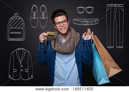 Pleasant shopping. Cheerful delighted young man holding his shopping bags and showing a discount card while standing against isolated black background.