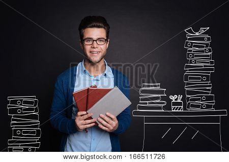 Organising data. Joyful handsome young man smiling and holding several personal organisers while standing near a desk and against isolated black background.