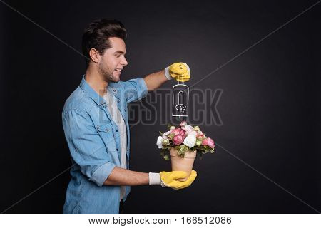 Watering plants. Delighted joyful young man smiling and watering flowers in a pot while standing against isolated black background.