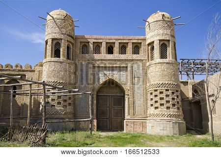 Old castle in Eastern Kazakhstan. Fortress the nomads. Walls and gate of the old fortress made of stone and lined with patterned tiles. Battle towers guarding the fortress. Asia