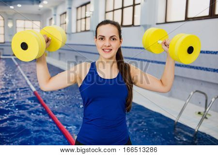Fit smiling woman holding foam water dumbbells at swimming pool. Aqua aerobics instructor