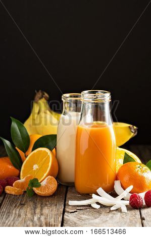 Fresh carrot, orange and coconut juices in glass bottles