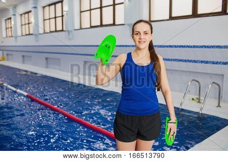 Portrait of a woman with blades for swimming, looking the camera. Female swimming instructor stands near the pool