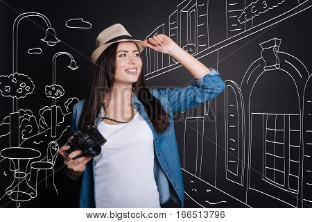 Enjoy traveling. Delighed young beautiuful woman smiling and holding photo camera while walking along the street
