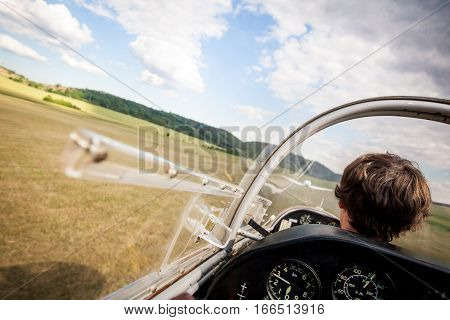 Landing of plane with pilot on natural Airport, pilot in cockpit of plane during landing