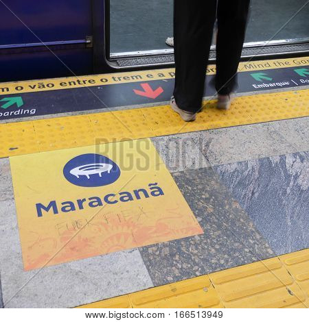 RIO DE JANEIRO BRAZIL - 26 JUNE 2014: The feet of a passenger waiting to board a Rio subway train to the Maracana football stadium. The sign has been defaced by a disgruntled soccer fan.