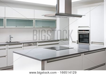 Luxurious modern kitchen with stainless steel appliances, minimalist kitchen with range hood, stove, microwave oven and sink