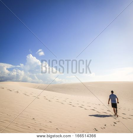 BARREIRINHAS, BRAZIL - 2 JULY 2014: A solitary man making his way through the hot sun and sand dunes of Maranhao Brazil.
