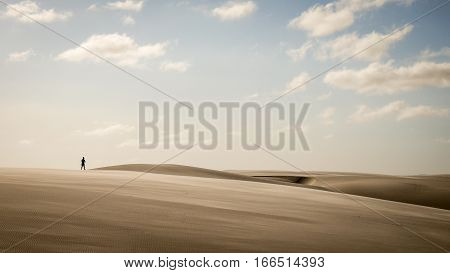Solitary Man Walking Through Sand Dunes