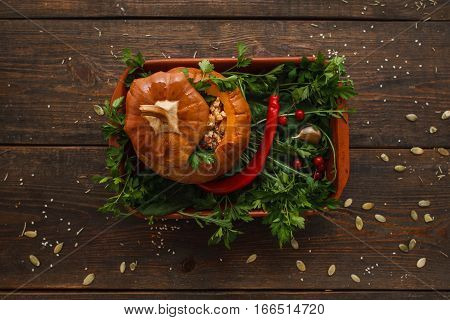 Baked stuffed pumpkin with fresh green flat lay. Top view on kitchen table with full prepared squash, Seasonal Halloween menu, vegetarian cuisine, healthy food concept