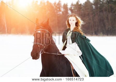 Young girl in white dress and green cape riding horse on snowy field near forest