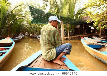 Mekong river Vietnam December 27 2016: Unidentified senior peasant man raw canoe on the Mekong river shore with boats after hard working day in Vietnam December 27 2016.