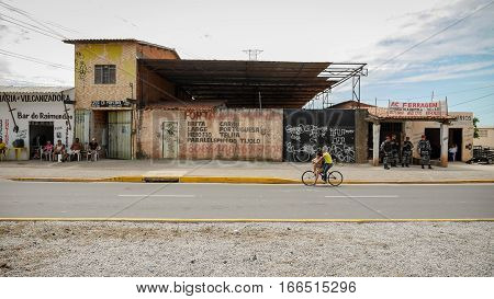 FORTALEZA BRAZIL - 4 JULY 2016: A roadside scene in Fortaleza Brazil with an old industrial building flanked by locals relaxing at a bar and uniformed police.