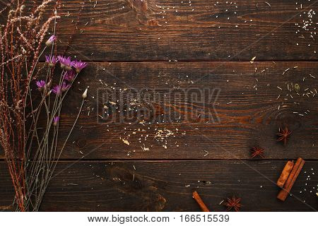 Wooden table with dry herbs flat lay free space. Top view on old rustic background with herbarium and spices, copy space for text. Craft, alternative medicine, magic concept