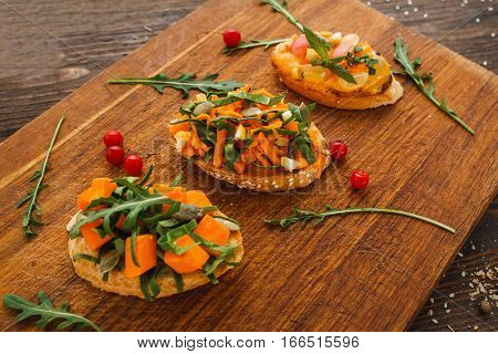 Tasty vegetarian canapes on wooden board. Tree portions of bruschetta with pumpkin and herbs. Recipe, healthy food, creative snack, seasonal snack concept