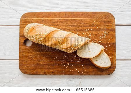 Crusty baguette on wooden board flat lay. Top view on kitchen table with cut fresh loaf of bread. Dining, dieting, appetizing concept