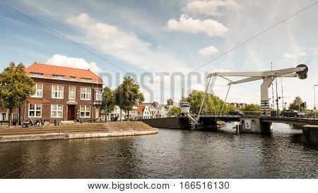 HAARLEM NETHERLANDS - 24 AUGUST 2014: A typical scene in the city of Haarlem Netherlands with a cantivelered Dutch canal bridge spanning the River Spaarne on a bright autumnal day.