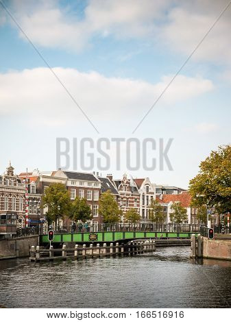 A typical swinging Dutch footbridge over the River Spaarne Haarlem Holland. The bridge allows boats to pass by pivoting on a central axis over the barriers to the left.