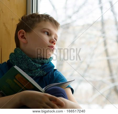 Boy with book looking through the window in winter day, indoors. Sick teen looks out the window.