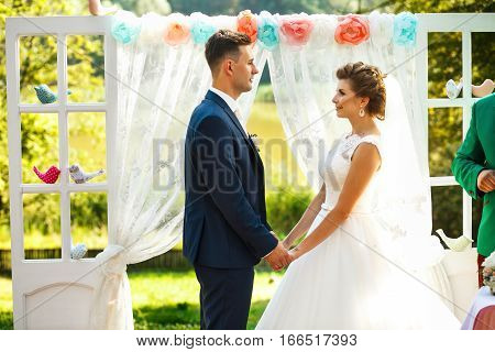Brides and groom standing near the wedding archway