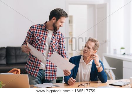 Discussion of the project. Nice diligent bearded man showing two sheets of paper to his colleague and discussing his ideas with him while working on the project together