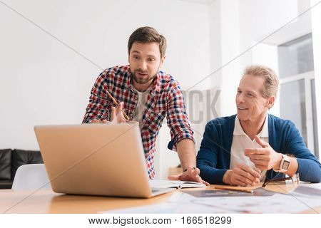 Interesting job. Handsome young hard working man holding a pencil and showing something to his senior colleague on the laptop while working with him at the office