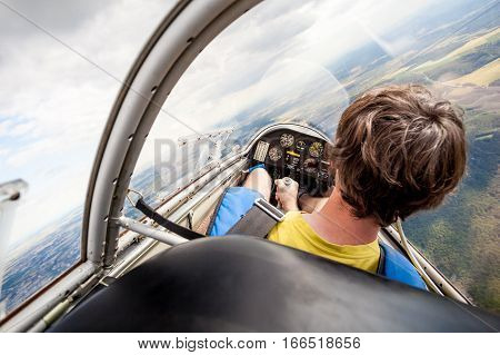 Pilot in cockpit of an aircraft which flies over landscape, lightweight glider flying just above ground